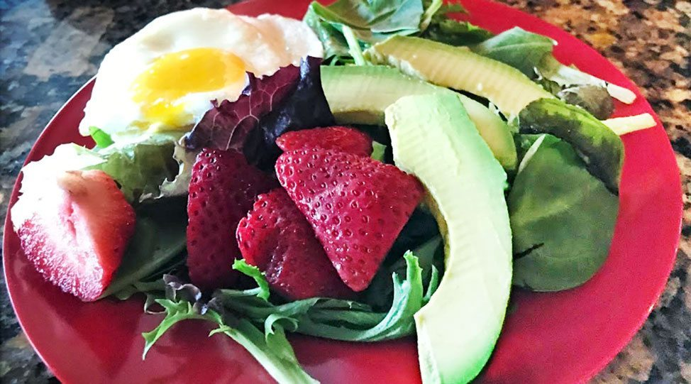 gluten free summer salad recipe spring mix with sliced strawberries and fried egg sunny side up